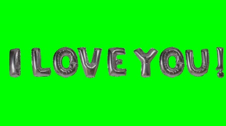 я тебя люблю : Word I love you from helium silver balloon letters floating on green screen