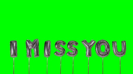 juffrouw : Word I miss you from helium silver balloon letters floating on green screen Stockvideo