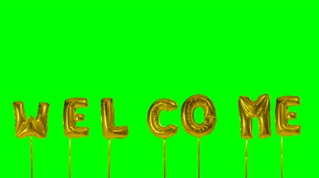 üdvözlet : Word welcome from helium golden balloon letters floating on green screen Stock mozgókép