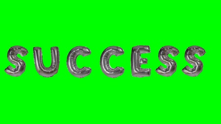 soletrar : Word success from helium silver balloon letters floating on green screen