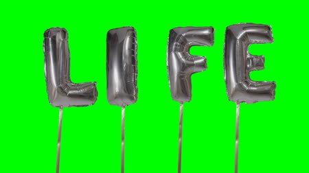 cytat : Word life from helium silver balloon letters floating on green screen