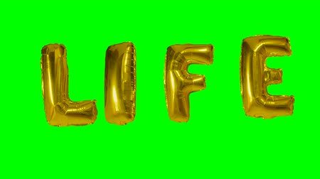 cytat : Word life from helium gold balloon letters floating on green screen Wideo