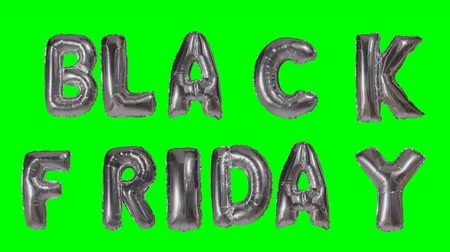 százalék : Word black friday from helium silver balloon letters floating on green screen