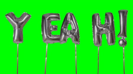 soletrar : Word yeah from helium silver balloon letters floating on green screen