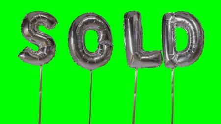 для продажи : Word sold from helium silver balloon letters floating on green screen Стоковые видеозаписи