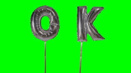 potvrzení : Word ok from helium silver balloon letters floating on green screen