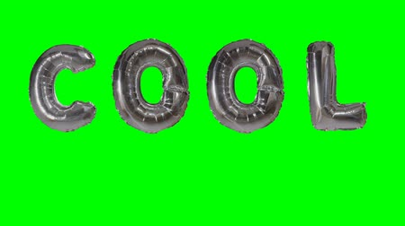 soletrar : Word cool from helium silver balloon letters floating on green screen