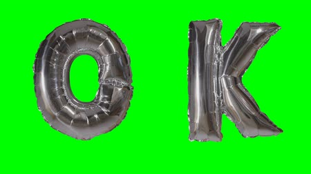 confirmação : Word ok from helium silver balloon letters floating on green screen
