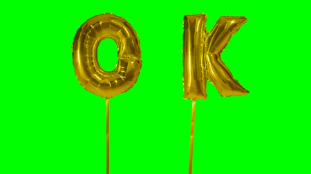 confirmação : Word ok from helium golden balloon letters floating on green screen Vídeos