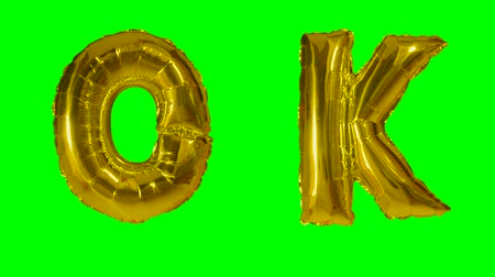 potvrzení : Word ok from helium gold balloon letters floating on green screen