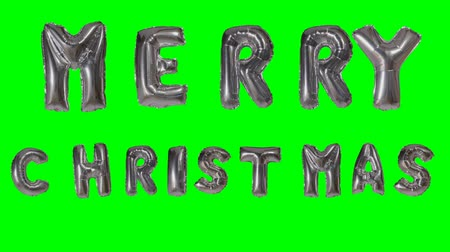 soletrar : Word merry Christmas greeting from helium silver balloon letters floating on green screen Vídeos