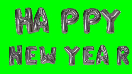 soletrar : Word Happy New Year greeting from helium silver balloon letters floating on green screen Vídeos