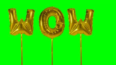 údiv : Word wow from helium golden balloon letters floating on green screen