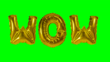 údiv : Word wow from helium gold balloon letters floating on green screen Dostupné videozáznamy