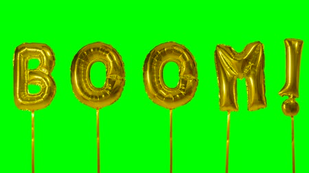 гул : Word boom from helium golden balloon letters floating on green screen Стоковые видеозаписи