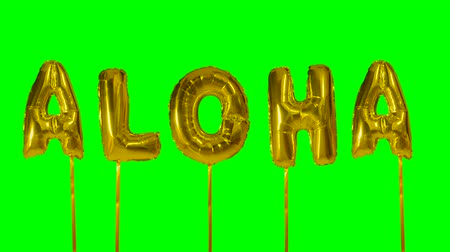 глянцевый : Word aloha from helium golden balloon letters floating on green screen