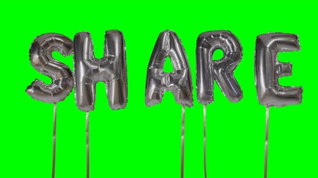 глянцевый : Word share from helium silver balloon letters floating on green screen Стоковые видеозаписи