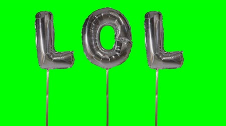 word balloon : Word lol from helium silver balloon letters floating on green screen