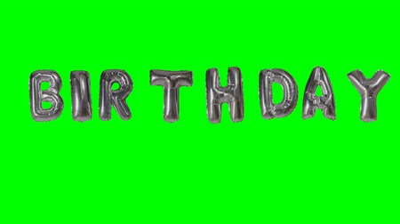 soletrar : Word birthday from helium silver balloon letters floating on green screen Vídeos