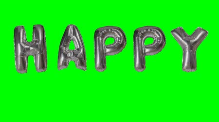 soletrar : Word happy from helium silver balloon letters floating on green screen