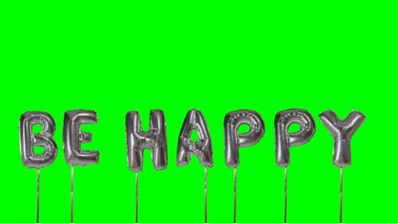 dilek : Word be happy from helium silver balloon letters floating on green screen