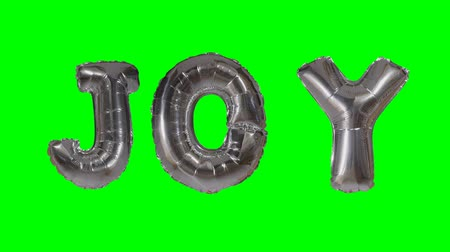 word balloon : Word joy from helium silver balloon letters floating on green screen