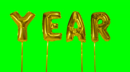 soletrar : Word year from helium golden balloon letters floating on green screen