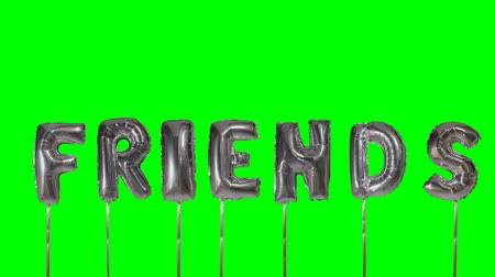 soletrar : Word friends from helium silver balloon letters floating on green screen