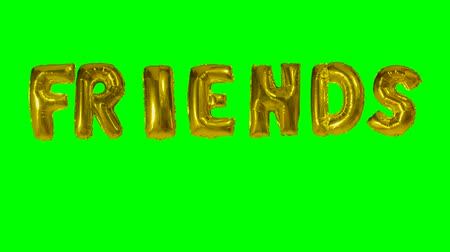 intimo : Word friends from helium gold balloon letters floating on green screen Filmati Stock