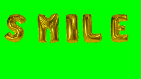 soletrar : Word smile from helium gold balloon letters floating on green screen Vídeos