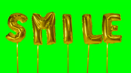 soletrar : Word smile from helium golden balloon letters floating on green screen Vídeos