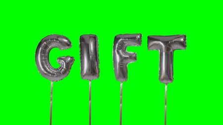 soletrar : Word gift from helium silver balloon letters floating on green screen