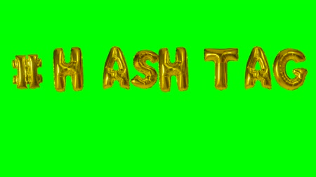 texto : Word hashtag from helium gold balloon letters floating on green screen