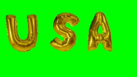 soletrar : Word USA from helium gold balloon letters floating on green screen