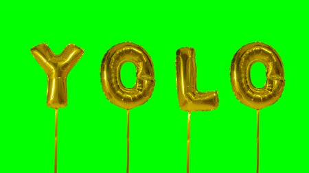 soletrar : Word YOLO from helium golden balloon letters floating on green screen