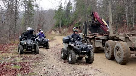 atv : Ukraine, Bukovel - November 20, 2019: a group of tourists from three ATVs in the forest rides along impassable roads and along a narrow dirt road, drives through and waits for oncoming traffic. Stock Footage