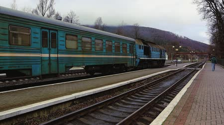 ayrılmak : Ukraine, Yaremche - November 20, 2019: the railway station, a train passes by, in the background mountains. Passengers leave the train on the platform of a small station in a sparsely populated city.