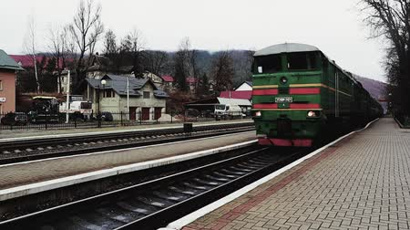 urlop : Ukraine, Yaremche - November 20, 2019: the railway station, a train passes by, in the background mountains. Passengers leave the train on the platform of a small station in a sparsely populated city.