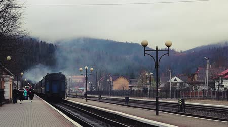 vagoneta : Ukraine, Yaremche - November 20, 2019: the railway station, a train passes by, in the background mountains. Passengers leave the train on the platform of a small station in a sparsely populated city.