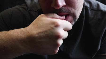 gnaw : Nervous man in a gray T-shirt bites his nail with his teeth, close-up. Head portrait of a man with a nervous expression biting his nails. A man eats nails, close-up, human problems and bad habits.