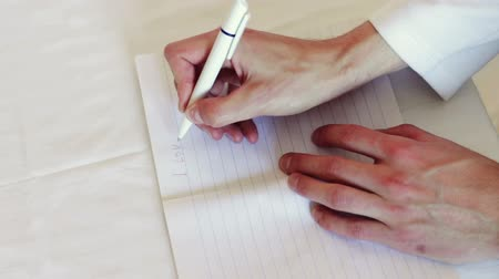 yazarak : Man hand holding a white pen and writes in a notebook in a line words and phrases.