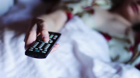 infra : Man lying on the sofa, bed, Press the button on the TV remote aimed at the TV. switches channels Stock Footage
