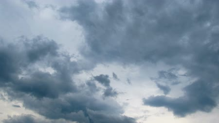 rainy : White, rain, gray, haze, dark, black, storm clouds moving across the blue sky against a background of the sun. Time lapse