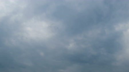 altostratus : White, rain, gray, haze, dark, black, storm clouds moving across the blue sky against a background of the sun. Time lapse