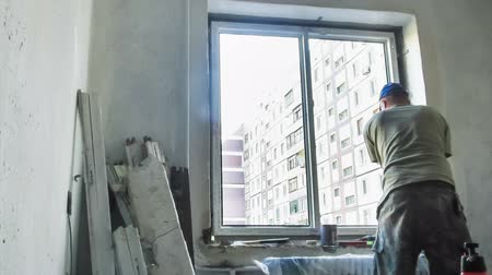 устанавливать : One worker takes in the room an old wooden window and plastic sets in his stead. The room renovation is carried out, the wall concrete, multi-storey house. Стоковые видеозаписи