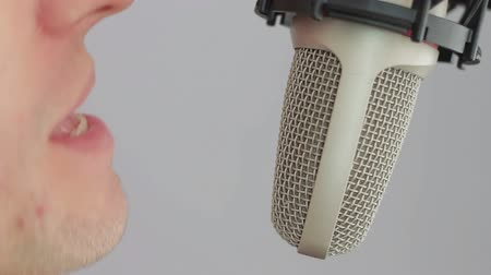 voz : Man expressive move, opens his mouth and sings a song near the condensor microphone in a recording studio on bright, white background. The microphone is fixed on a microphone stand holder spider.