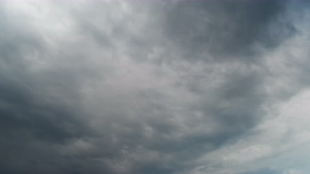 popisný : White, rain, gray, haze, dark, black, storm clouds moving across the blue sky against a background of the sun. Time lapse
