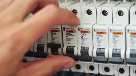 осмотр : Man hand turns on and off Electricity Power Fuse Circuit in the panel. Switching electrical machines in different positions. 380 volts. High voltage.
