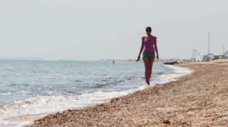outside : The girl in green shorts and a red T-shirt with slaps in the hands, there is a beautiful on the beach, to the left of her worries sea and clean sandy beach on the right.