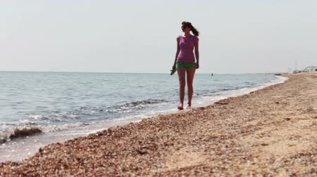 preocupações : The girl in green shorts and a red T-shirt with slaps in the hands, there is a beautiful on the beach, to the left of her worries sea and clean sandy beach on the right.